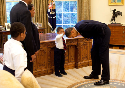 President Obama bent over so the son of a White House staff member can pat his head during a 5-8-09 family visit to the Oval Office.
